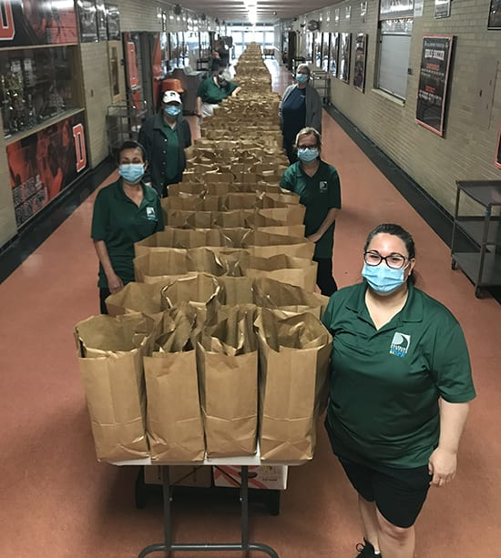 Food service workers stand by a long row of tables covered with paper bags full of food.