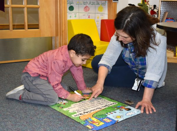 A GSRP teacher at Cotter School in Dearborn sits on the floor to work one-on-one with a student early in 2020.