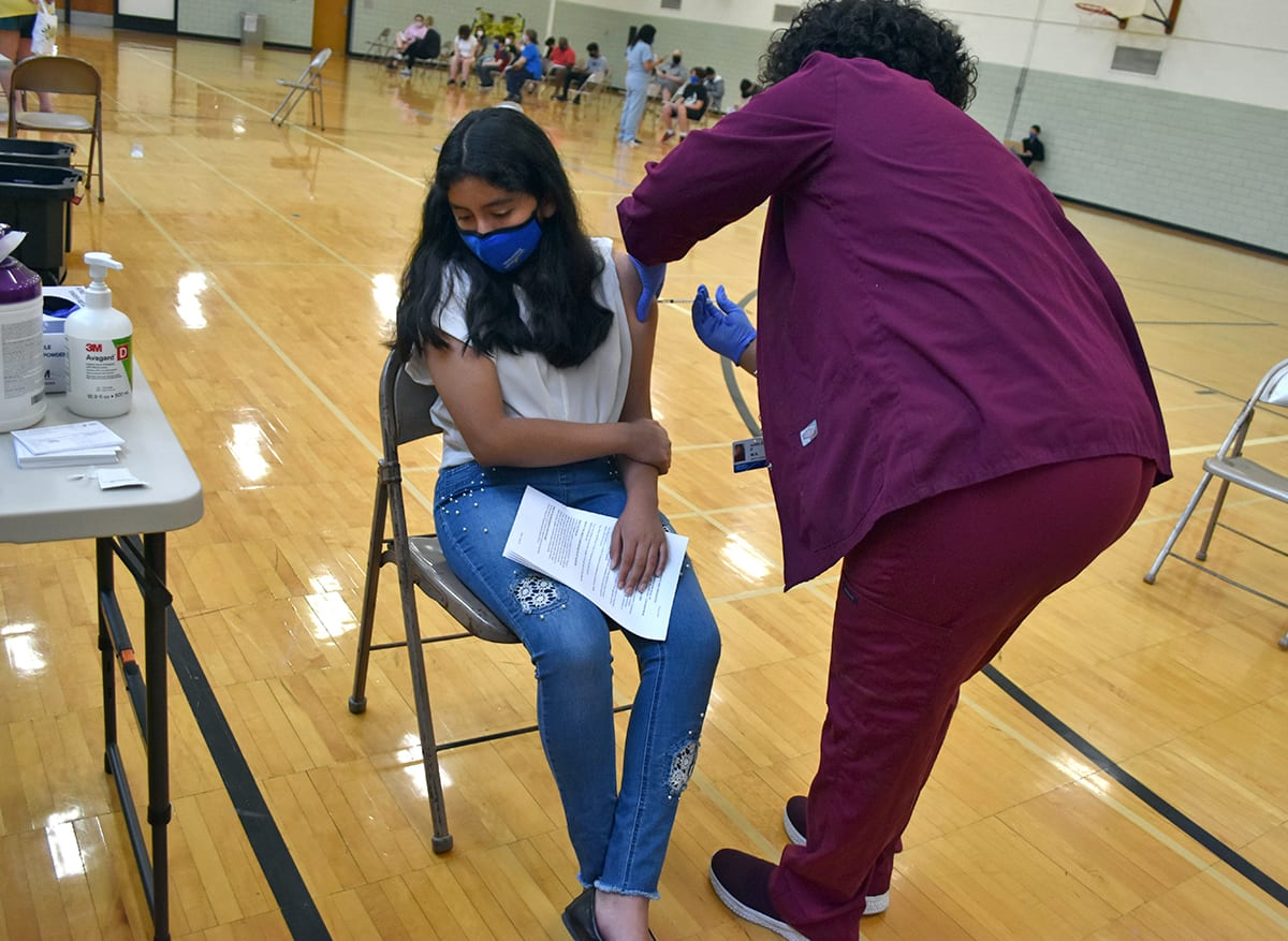 A girl looks away while getting her COVID vaccination at Edsel Ford High School in May.