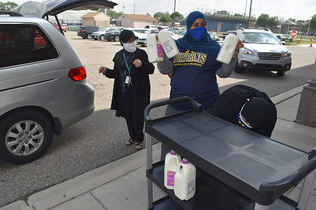 Women load milk and food into a mini van at Fordson High School in June 2021.